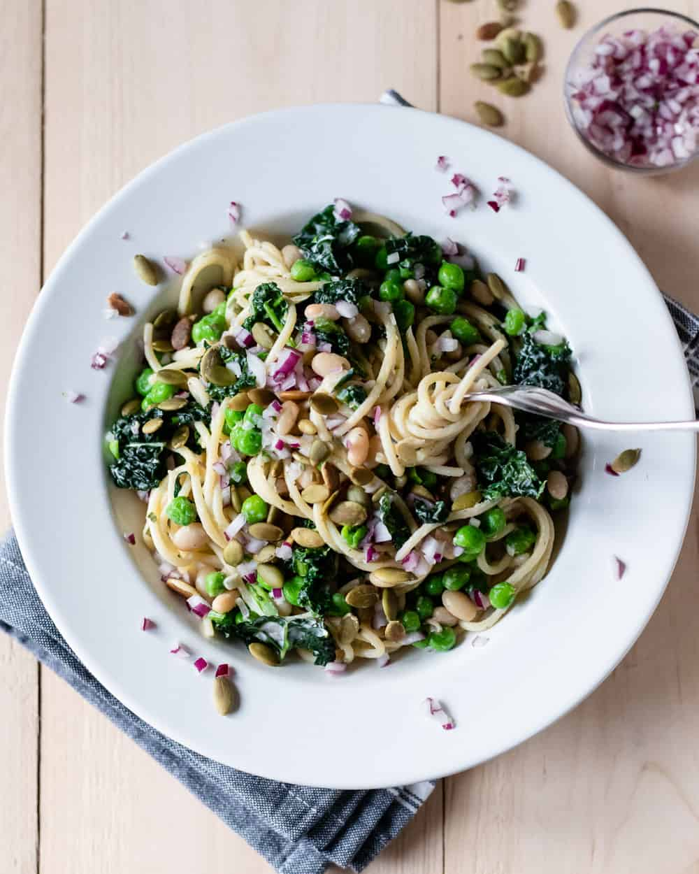 Pasta with green peas and dino kale in a bowl