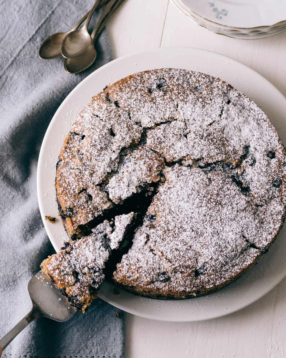 Cake made with blueberries with a dusting of powdered sugar.