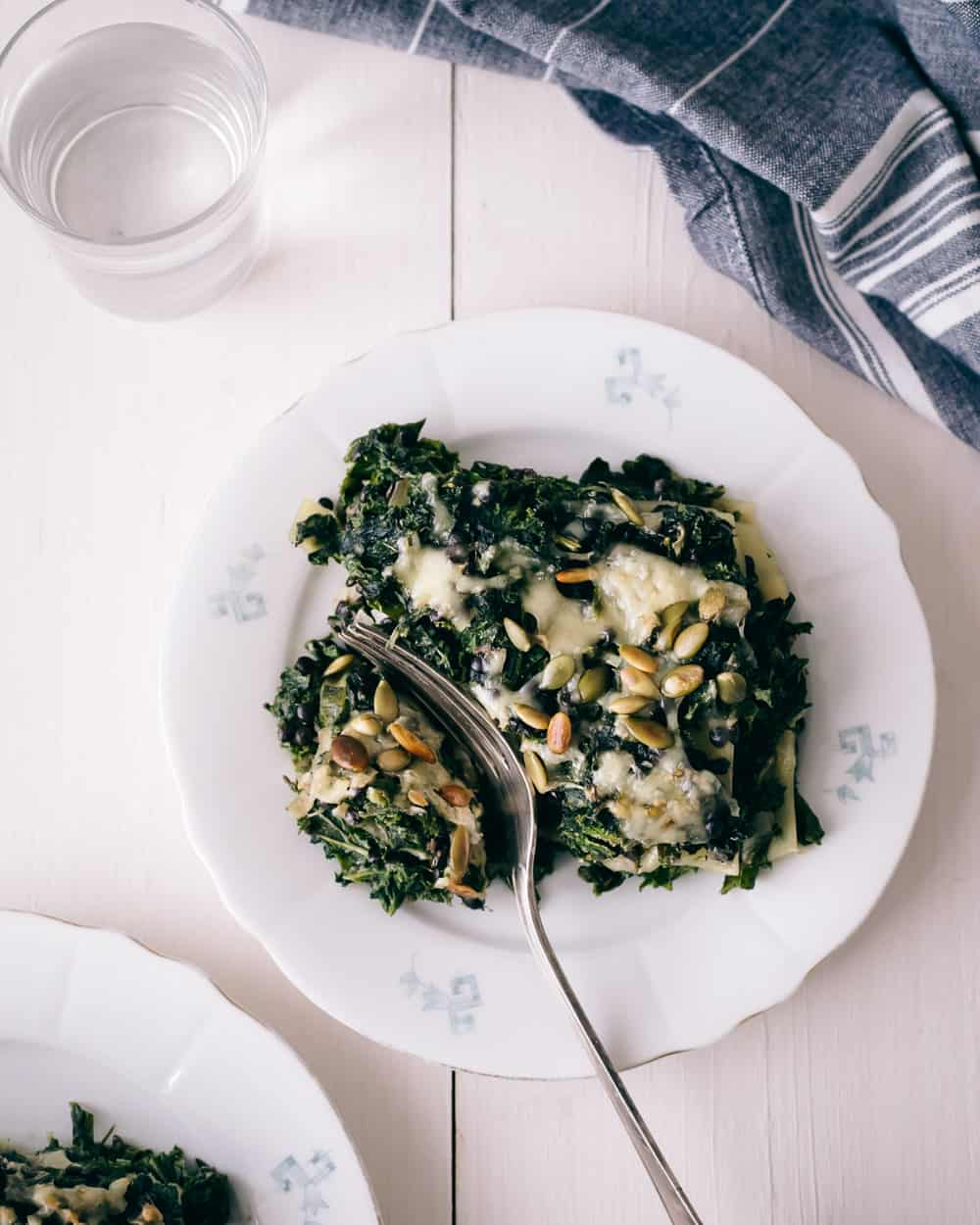 A plate with kale lasagna topped with pumpkin seeds